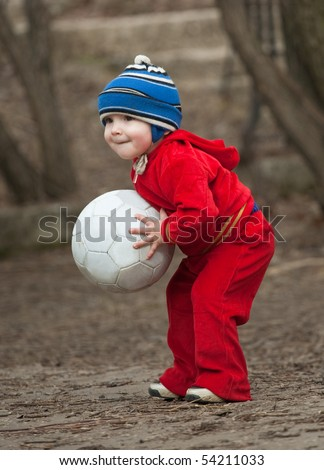 Little boy plays with football ball outdoor - stock photo