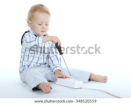 little boy plays with plug and screwdriver