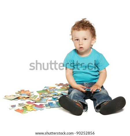 little boy plays with puzzle isolated on white