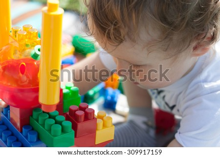 little boy plays with the constructor
