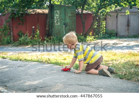 little boy plays with toy car. Adorable kid boy playing with cars and toys outdoor. Funny child having fun. Colorful playground on background. Family, holiday, kids lifestyle concept.