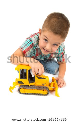 little boy plays with toy tractor