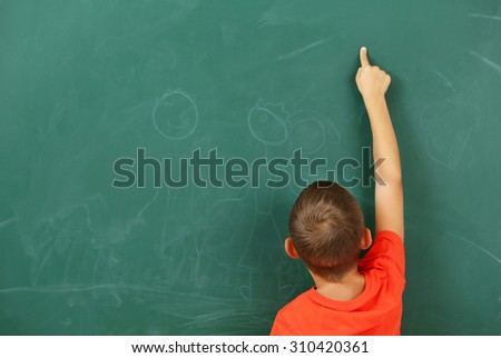 Little boy pointing at something at black chalkboard in classroom