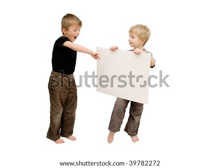 Little boy points excitingly to blank card which his brother is holding. - stock photo