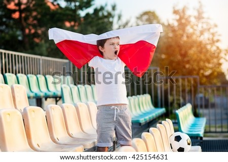 Little boy - Polish football team fan - supporter with Polish flag on the stadium