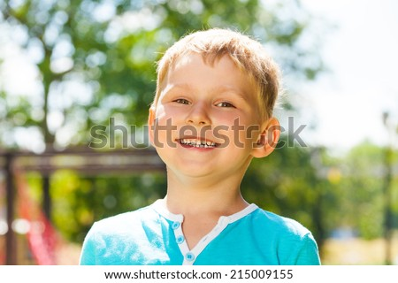 Little boy portrait with big smile outside - stock photo