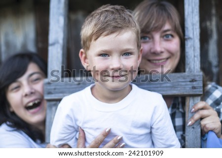 Little boy poses for the camera, with his older sister and mother in a blur in the background, outdoors.