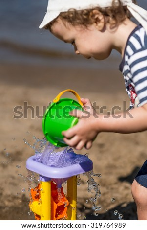 little boy pours water on the water mill on the beach, summer