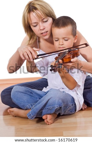 Little boy practicing the violin sitting on the floor with a woman - isolated - stock photo