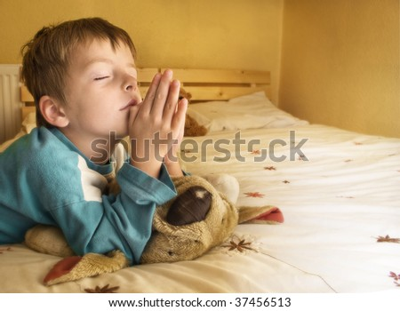 Little boy praying at bedtime. - stock photo
