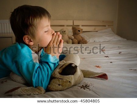 Little boy praying at bedtime - stock photo