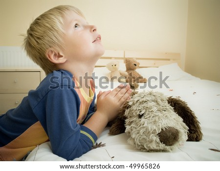 Little boy prays in the bedroom by the bed. - stock photo