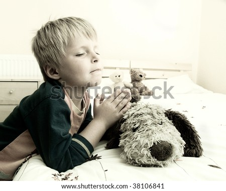 Little boy prays with a look of desperation on his face. - stock photo