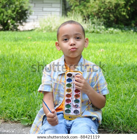 Little Boy Puckering Lips looking at camera holding paint set sitting on grass