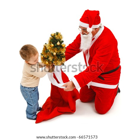 Little boy putting a small, decorated Christmas tree in Santa Claus's bag - stock photo