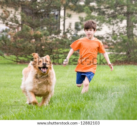 Little Boy Racing the Dog - stock photo
