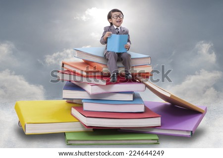 Little boy reading a book on pile of books  - stock photo