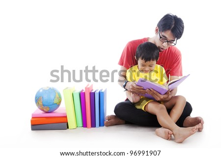 Little boy reading a geography book with dad shot in studio isolated on white
