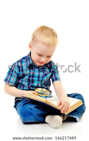 little boy reading book with magnifying glass