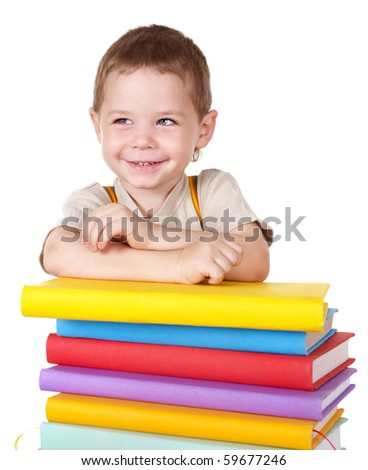 Little boy reading pile of books. - stock photo