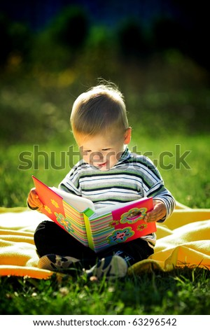 little boy reads a book - stock photo