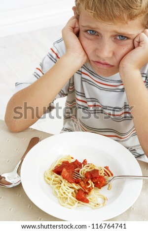 Little boy rebelling against his food as he sits looking glumly at the plate of spaghetti bolognaise that he has been served - stock photo