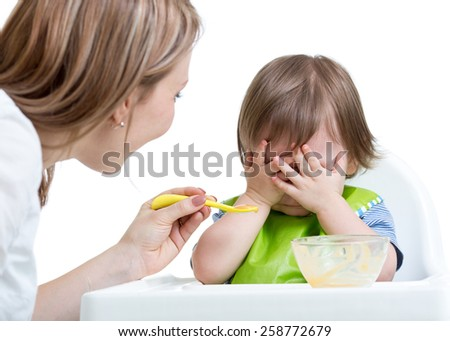 Little boy refuses to eat closing face by hands, isolated on white - stock photo
