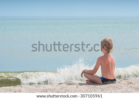 Little boy relaxing in lotus yoga pose on a beach sand with waves and seascape as background.