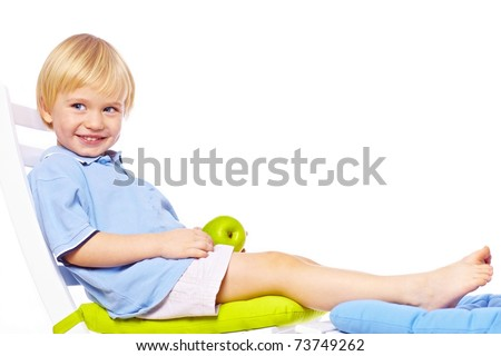 Little boy relaxing on chair with apple isolated over white back - stock photo
