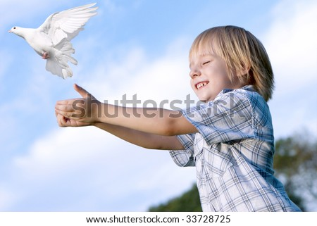 Little boy releasing a white pigeon in the sky. - stock photo