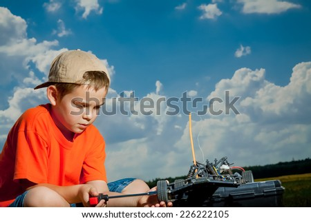 Little boy repaire the radio control car outdoor near field - stock photo