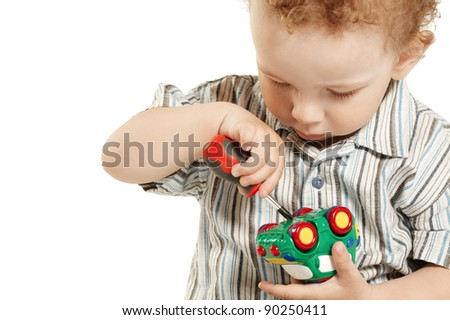little boy repairs toy car - stock photo