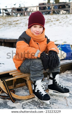Little boy resting on a sled after skating - stock photo