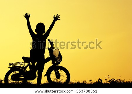 Little boy riding bike, Asian kid ,Silhouette a kid at the sunse