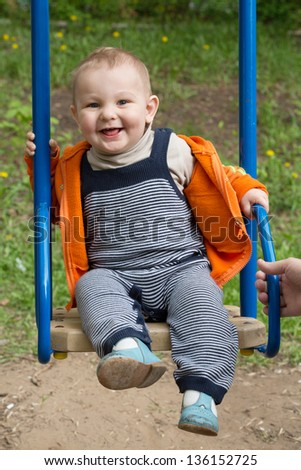 Little boy riding on a swing and smiling - stock photo