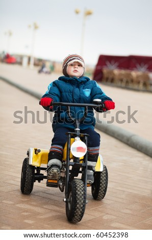 Little boy riding tricycle in a cold winter day - stock photo