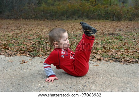 Little boy role plays the exercises he has seen his mom doing.  He is concentrating and lifting his legs into the air as he sits on the sidewalk and leans backwards. - stock photo