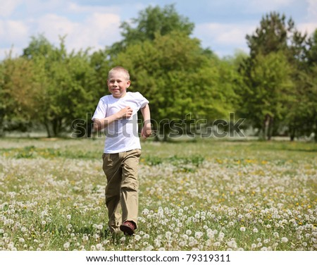little boy running and playing in the summer park