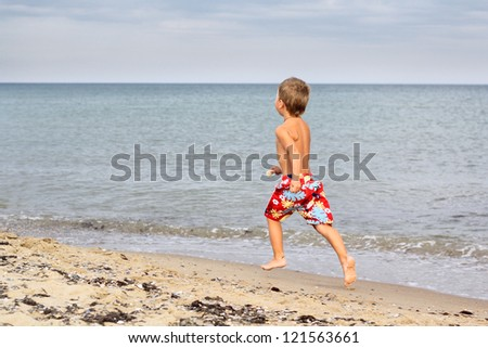 Little boy running at the seashore