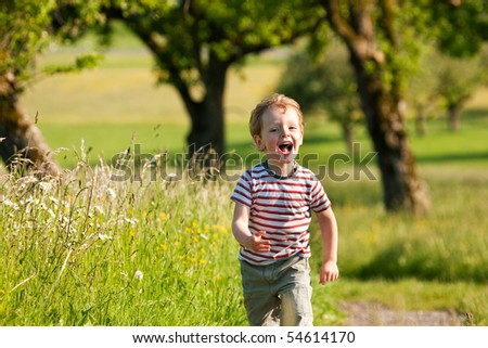 Little boy running down a dirtpath in a beautiful landscape in summer, very light and happy scene - stock photo