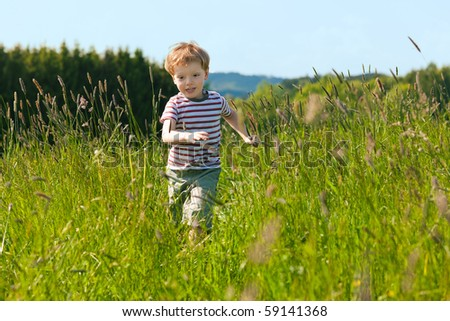 Little boy running down a meadow in a beautiful landscape in summer, very light and happy scene - stock photo
