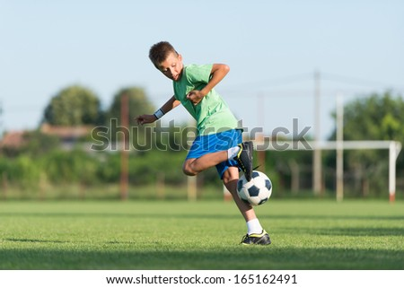 little boy running dribbling on the sports field - stock photo