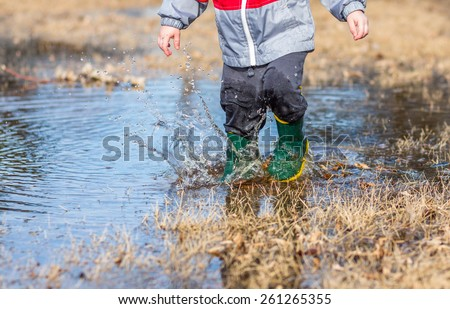 Little boy running in puddles wearing rain boots. - stock photo