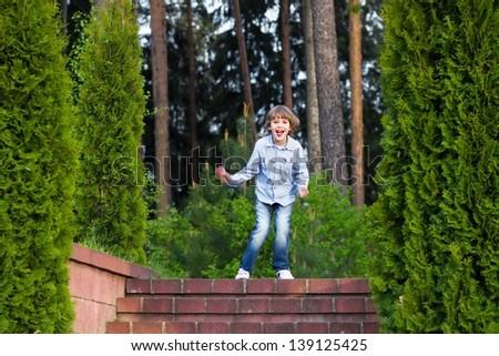 Little boy running on beautiful garden stairs - stock photo