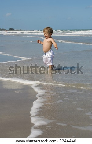 Little boy running out of water on a beach. - stock photo
