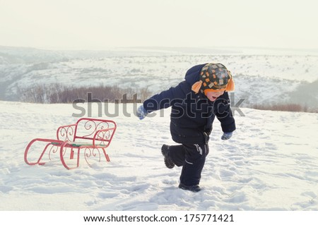 Little boy running through snow dragging a colourful orange toboggan behind him as he enjoys his freedom in the winter countryside - stock photo