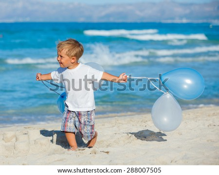 Little boy running with bunch of ballons on the beach