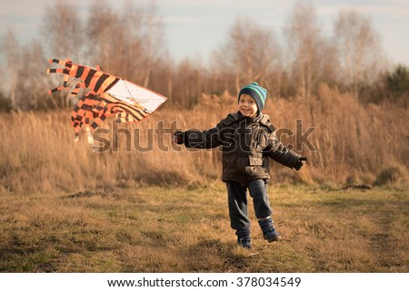 Little boy running with kite in the field on winter sunny day - stock photo