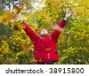 little boy's throwing autumn leaves in the forest - stock photo