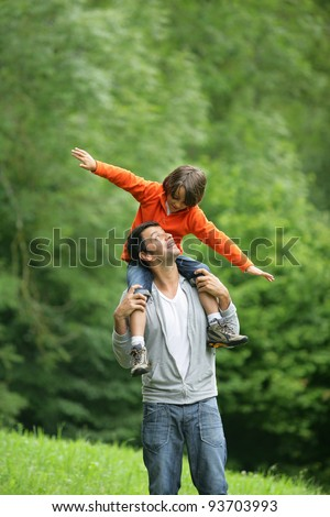 Little boy sat on father's shoulders - stock photo